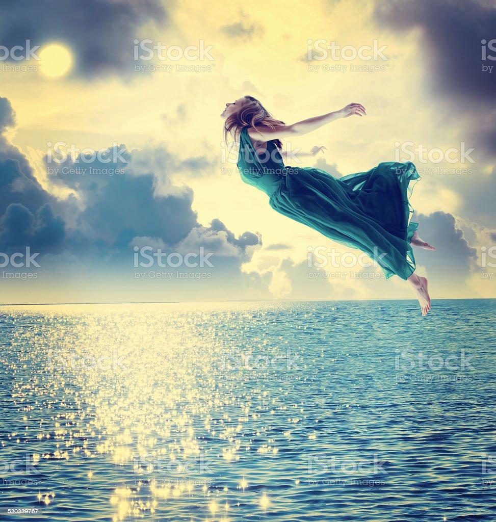 Beautiful girl jumping into the night sky stock photo