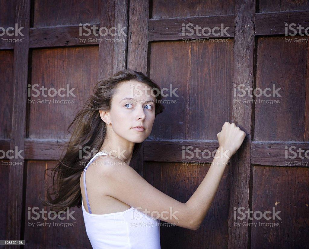 Beautiful Girl Knocking On a Door stock photo