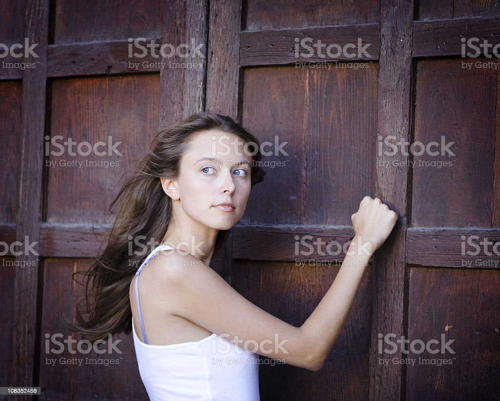 Beautiful Girl Knocking On a Door stock photo