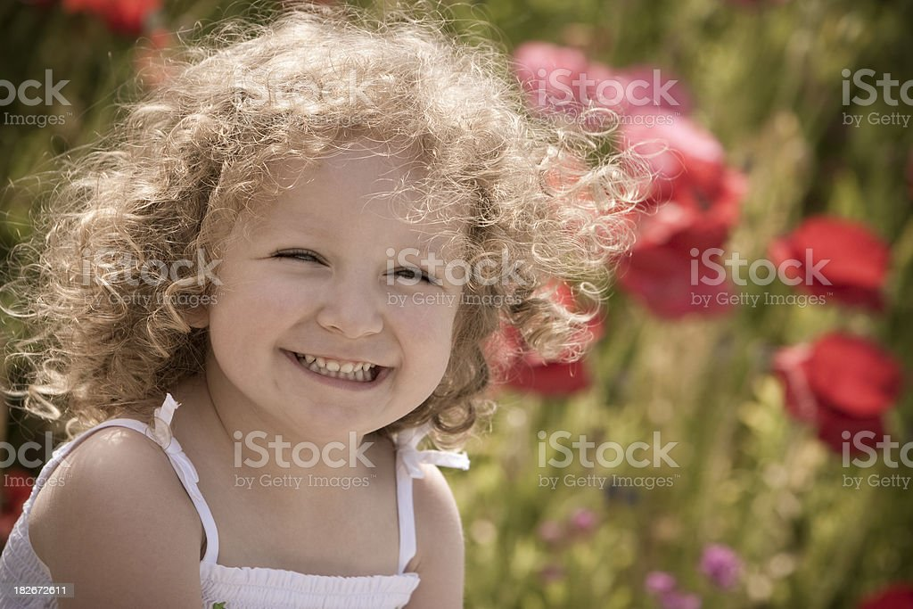 Beautiful girl laughing in poppy field royalty-free stock photo