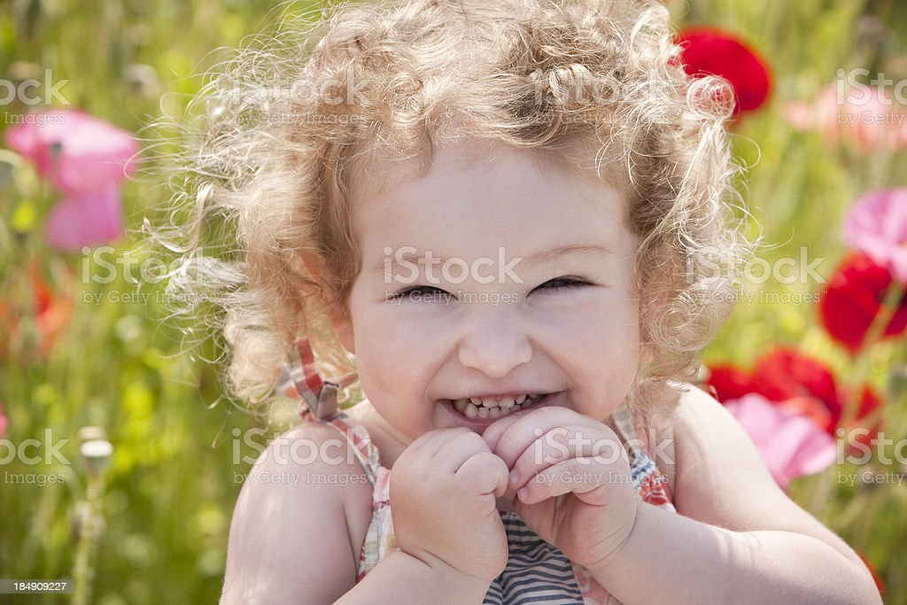 Beautiful girl laughs in poppy field royalty-free stock photo