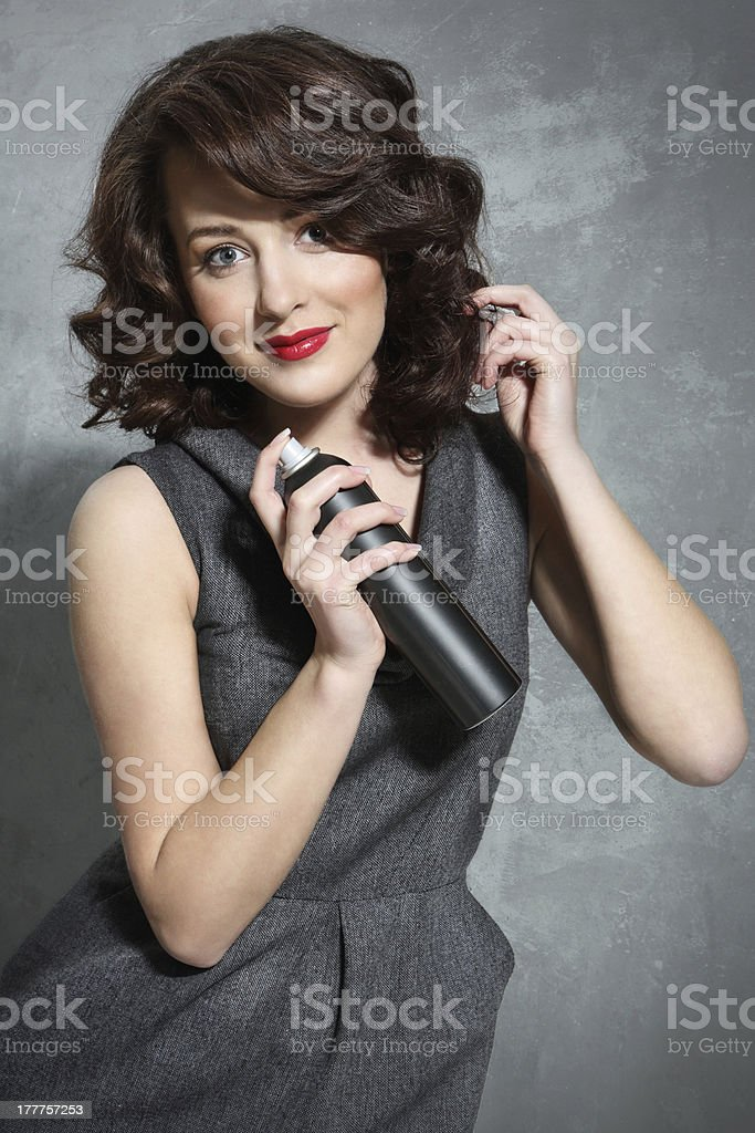 Beautiful girl laying fixes using hairspray royalty-free stock photo