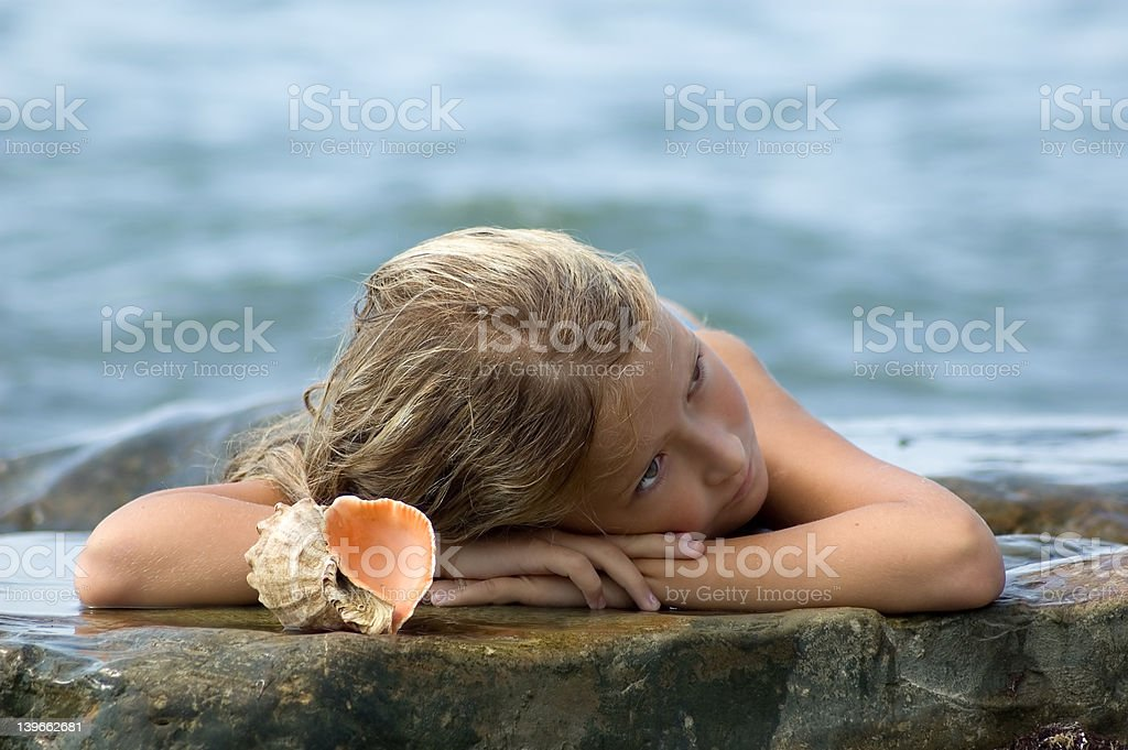 Beautiful girl laying on the rock with a seashell royalty-free stock photo
