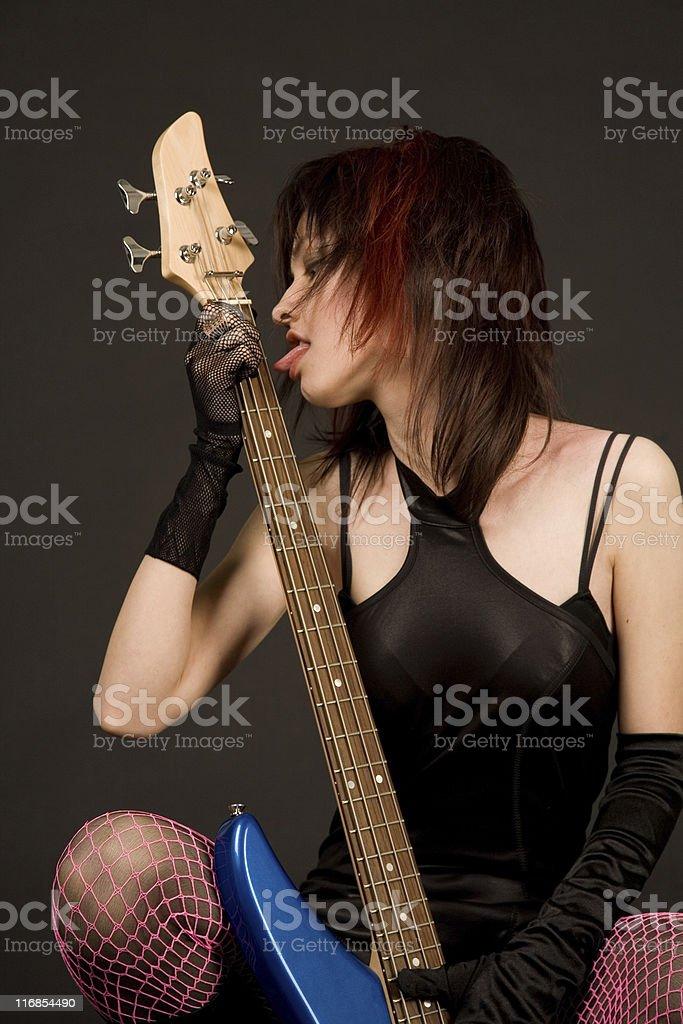Beautiful girl licking guitar royalty-free stock photo