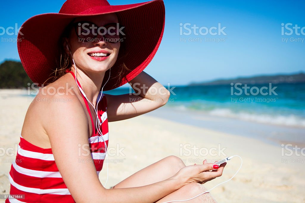Beautiful girl listening to music on the beach stock photo