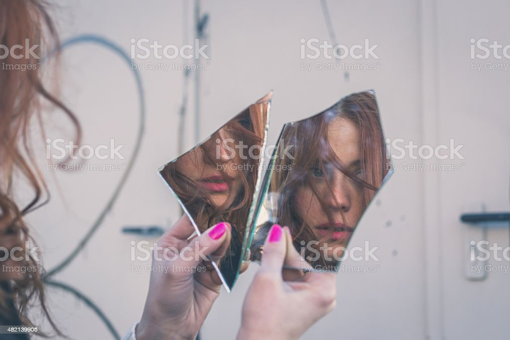 Beautiful girl looking at herself in a mirror stock photo