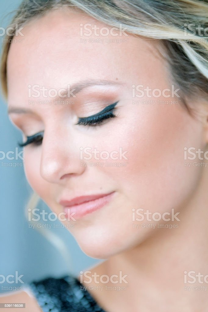 Beautiful girl looking down with clear skin,perfect make-up stock photo