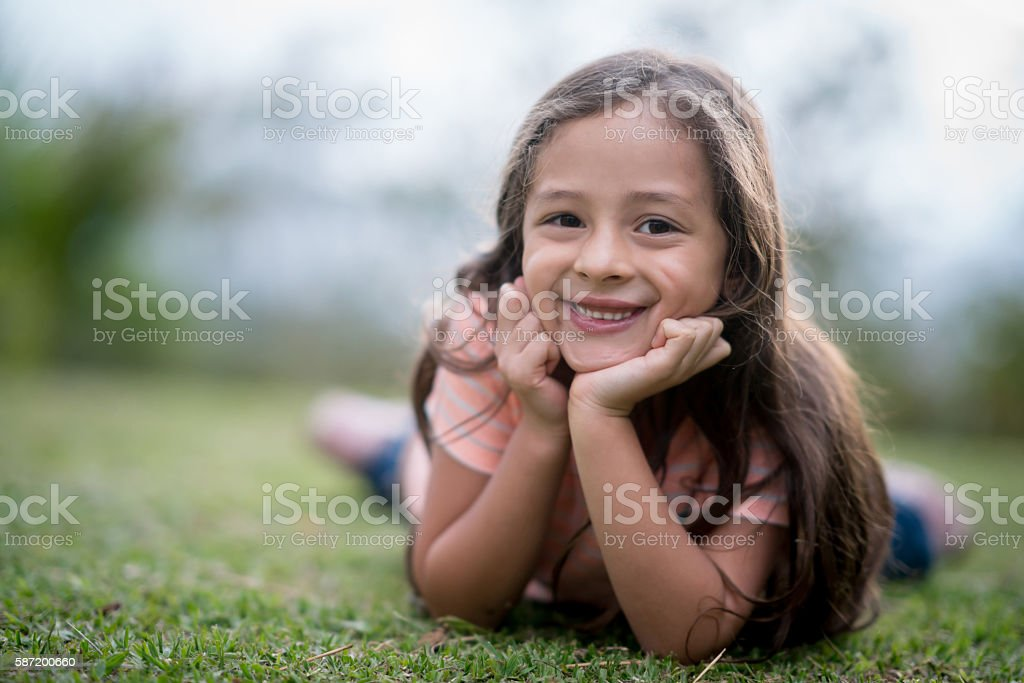Beautiful girl lying at the park stock photo