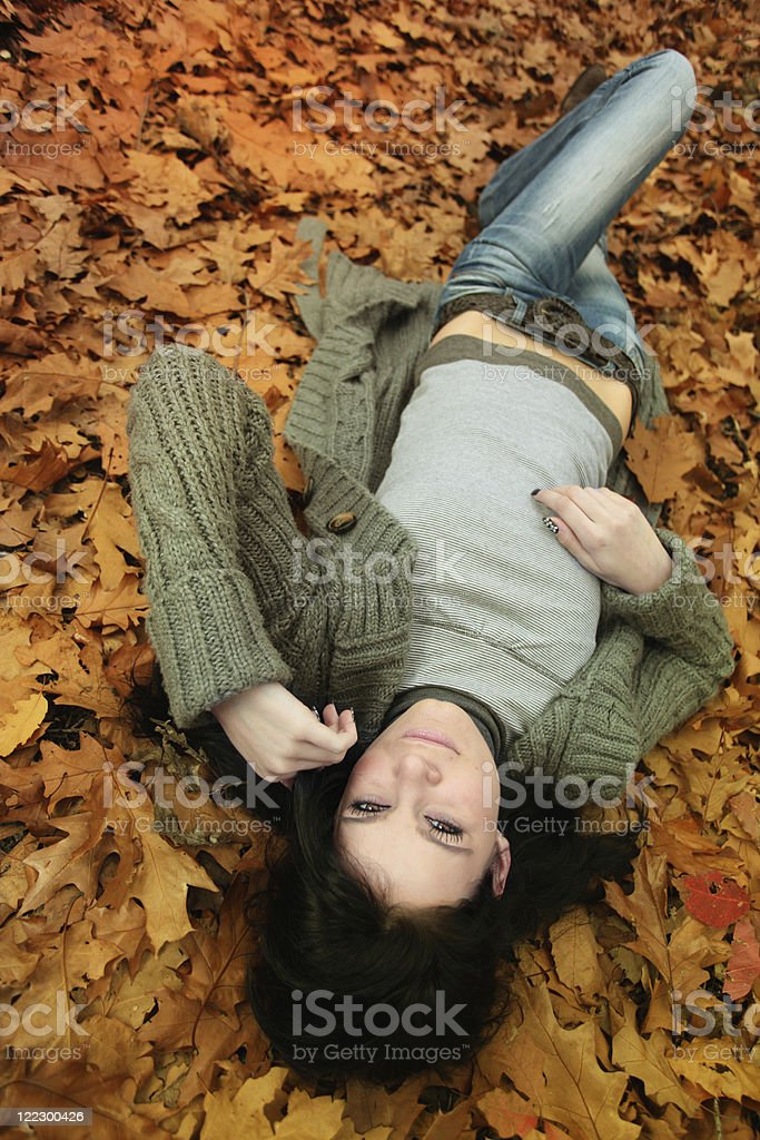 beautiful girl lying on the ground covered with leaves stock photo