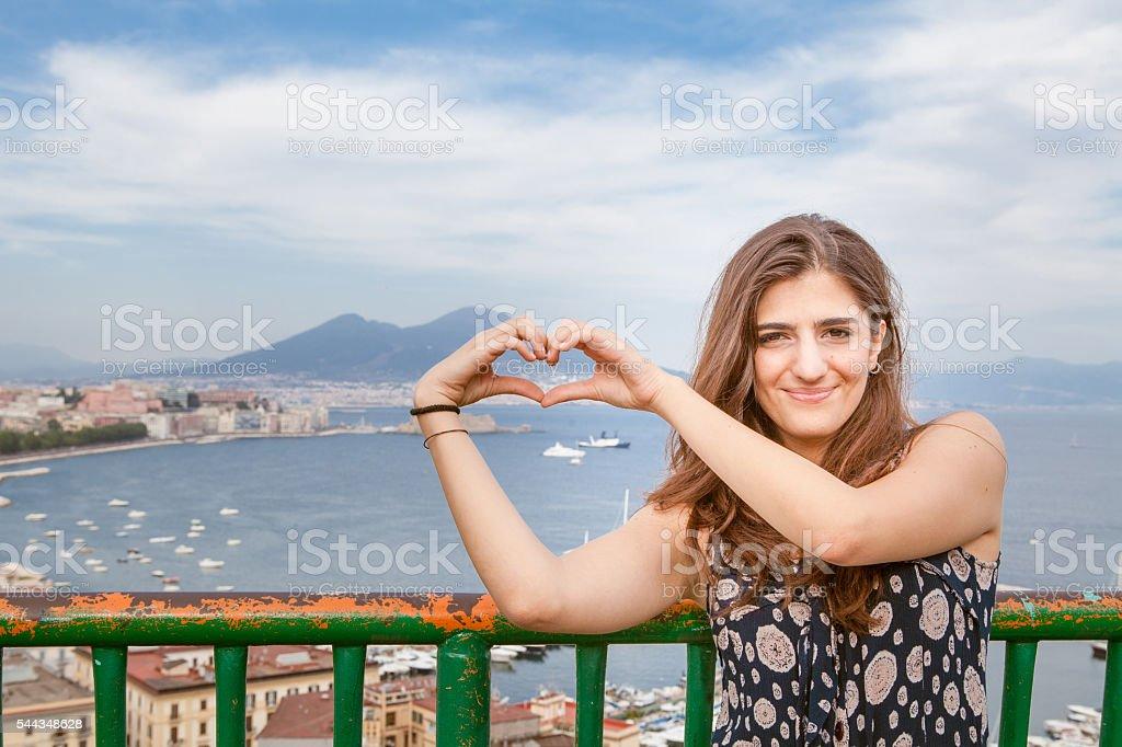 Beautiful Girl Making Heart Shape on Naples City Background stock photo
