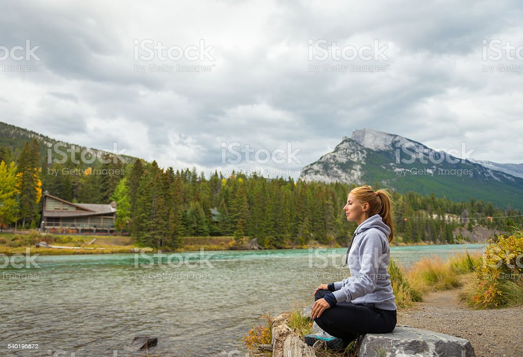 Beautiful girl meditating in the mountains stock photo