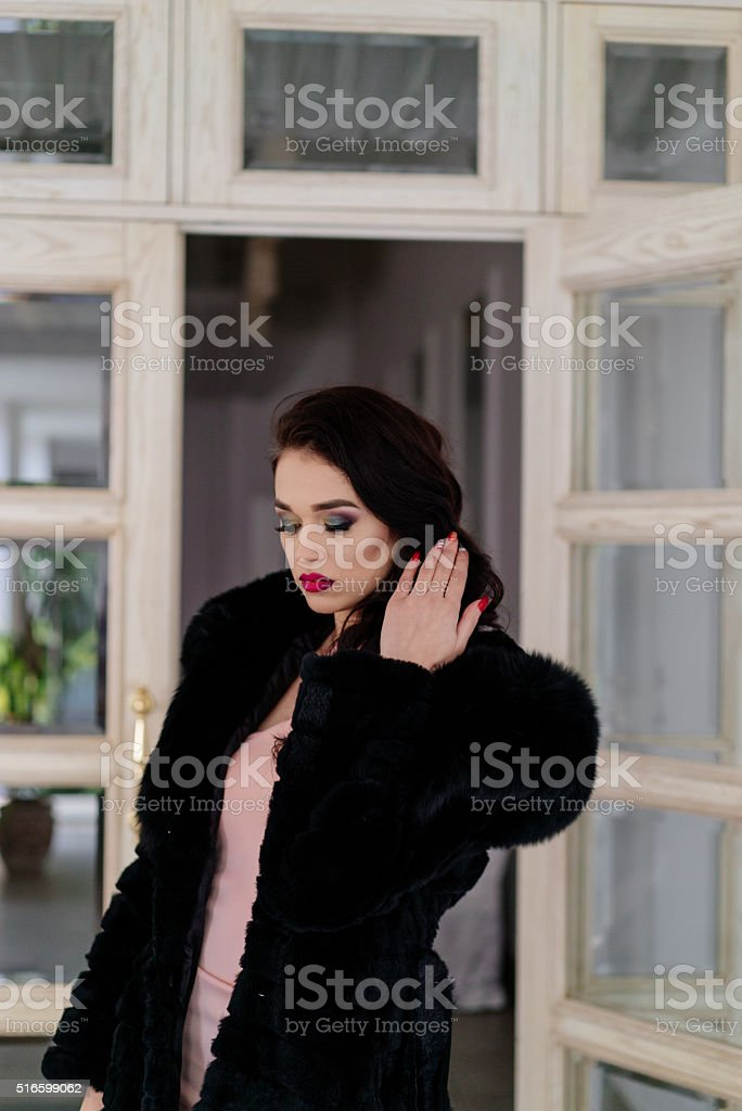 Beautiful girl model in a black coat stock photo