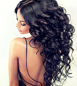 Beautiful girl model with long black curled hair.