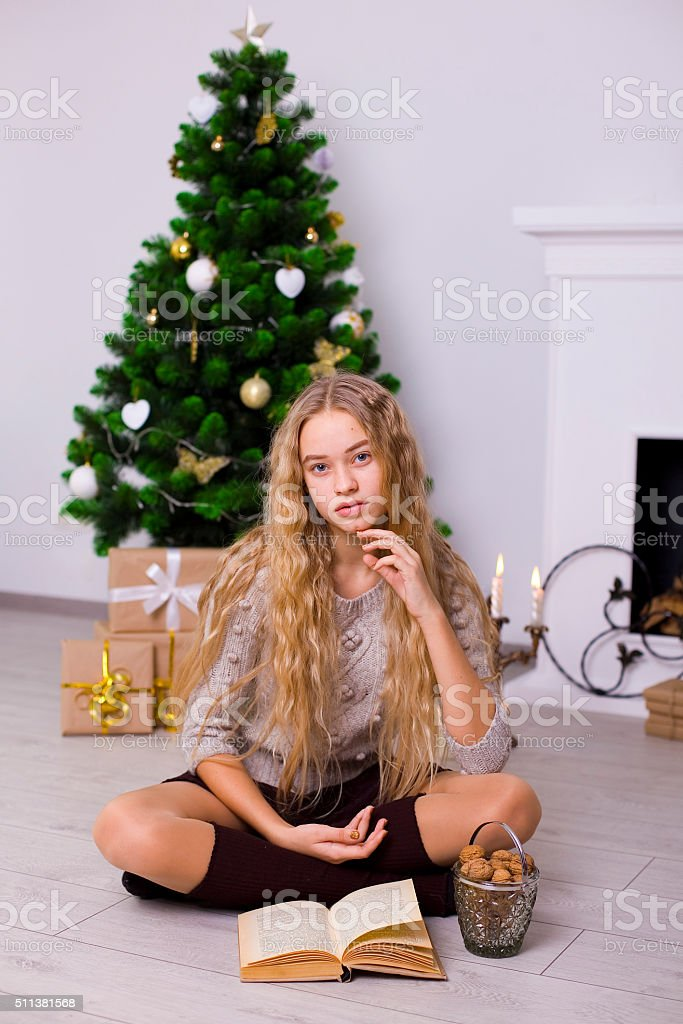 beautiful girl near a Christmas tree in the room stock photo
