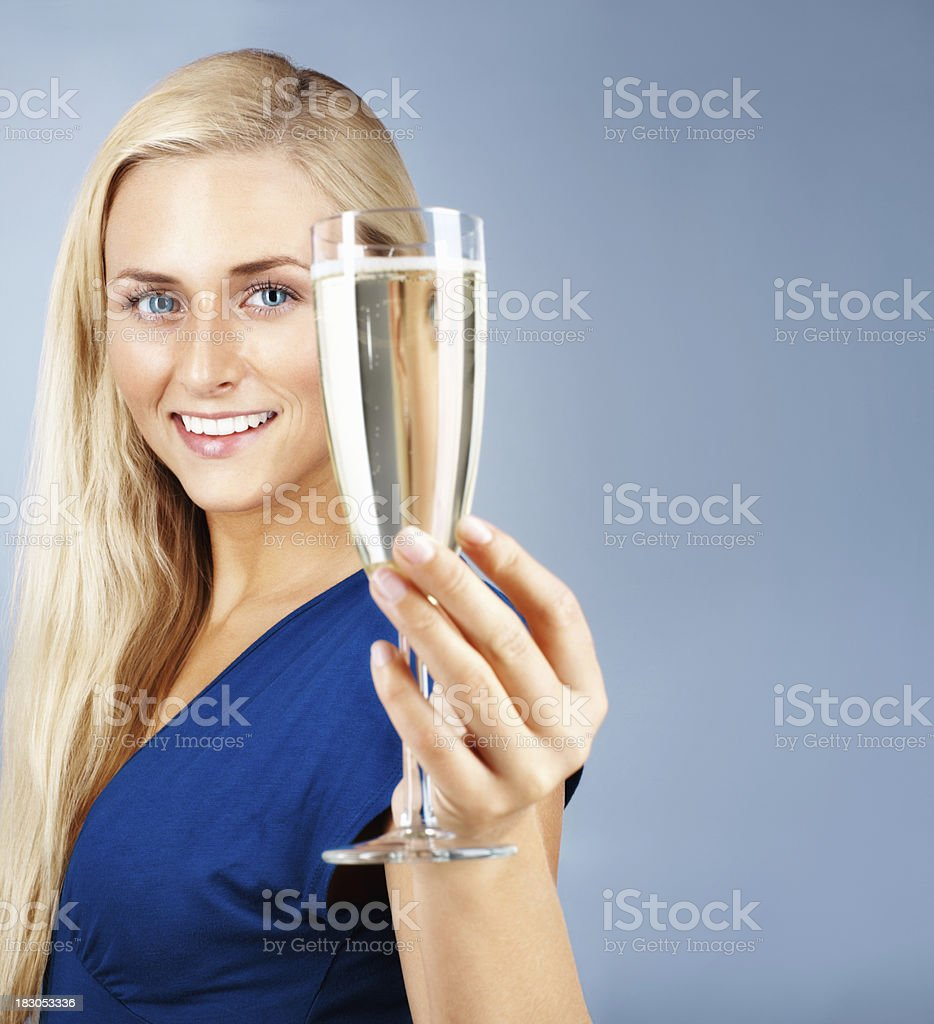 Beautiful girl offering you a drink against colored background royalty-free stock photo
