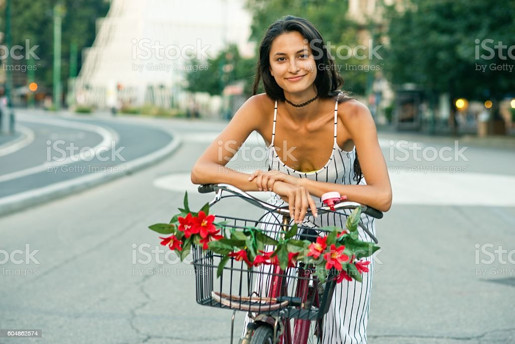 Beautiful girl on a bicycle looking at camera. stock photo