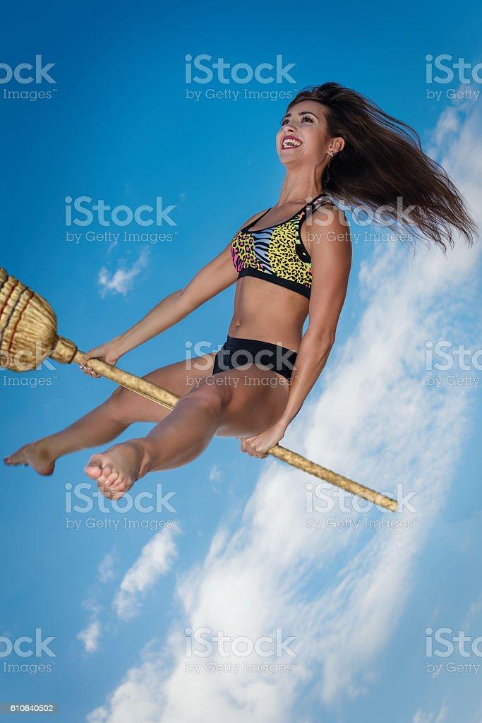 Beautiful girl on a broomstick stock photo