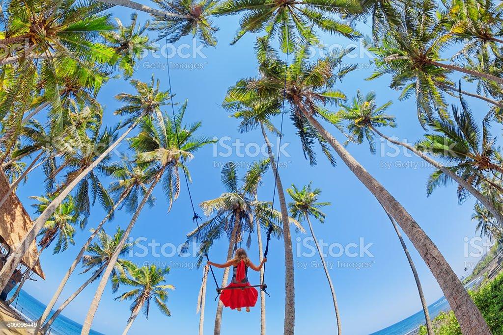 Beautiful girl on rope swing among coconut palms on beach stock photo