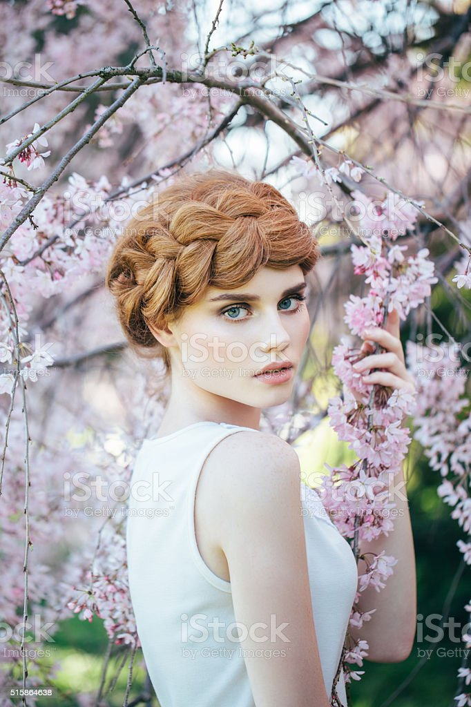 Beautiful girl on the background of  spring bush stock photo