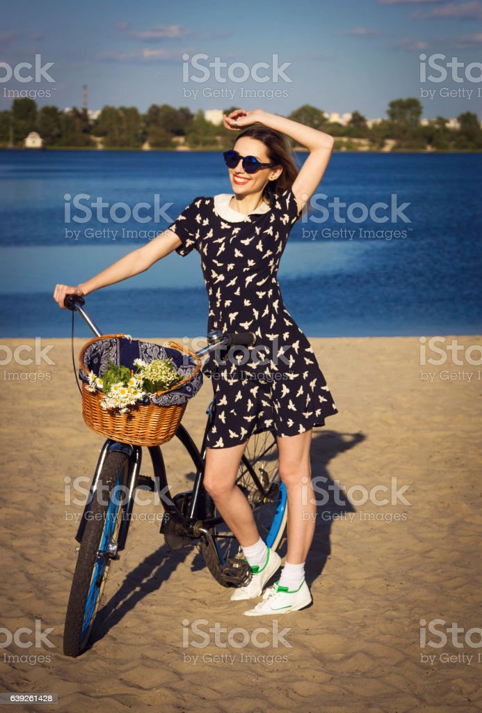 Beautiful girl on the beach with cruiser bicycle stock photo