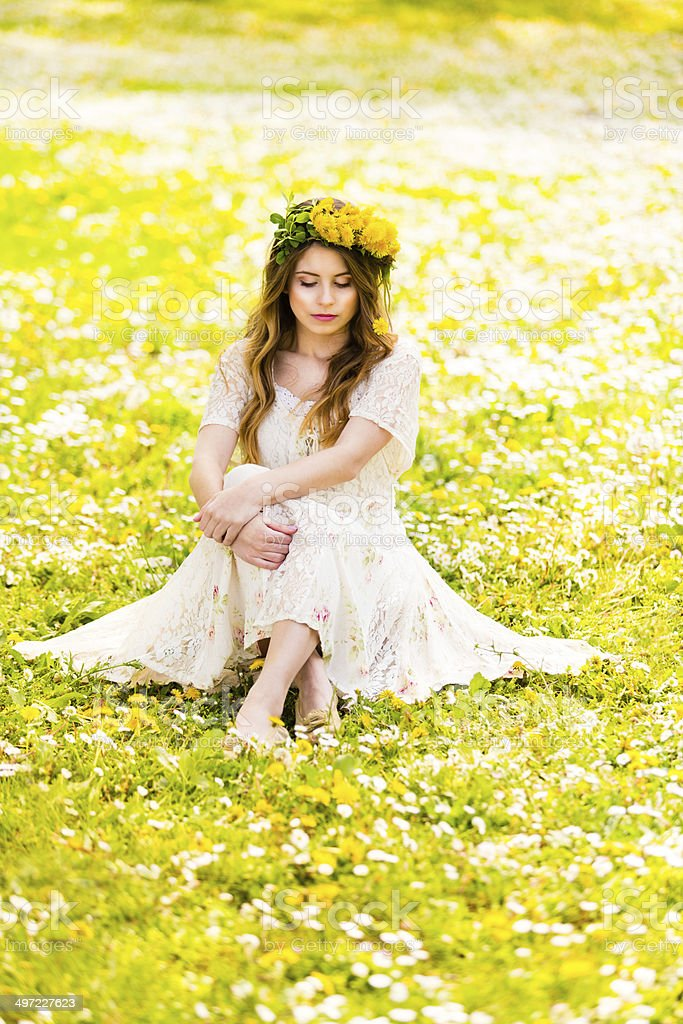 Beautiful girl on the grass with a flower wreath stock photo