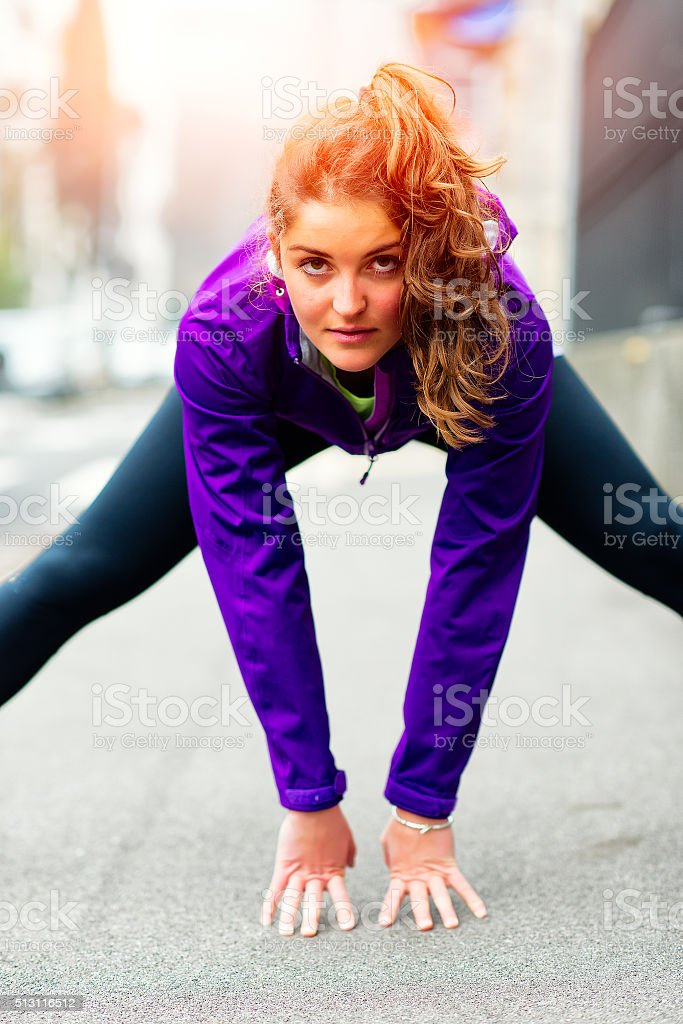 Beautiful girl on the sidewalk makes gymnastics stock photo