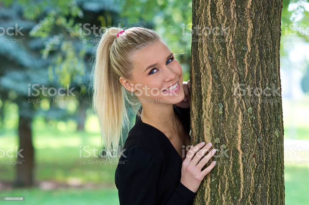beautiful girl outside next to tree stock photo