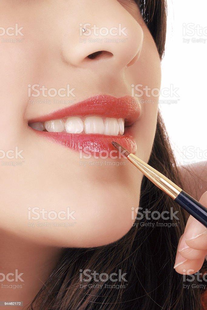 Beautiful girl painting her lips stock photo