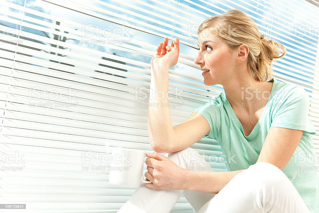 beautiful girl peeks with cup near venetian blind royalty-free stock photo