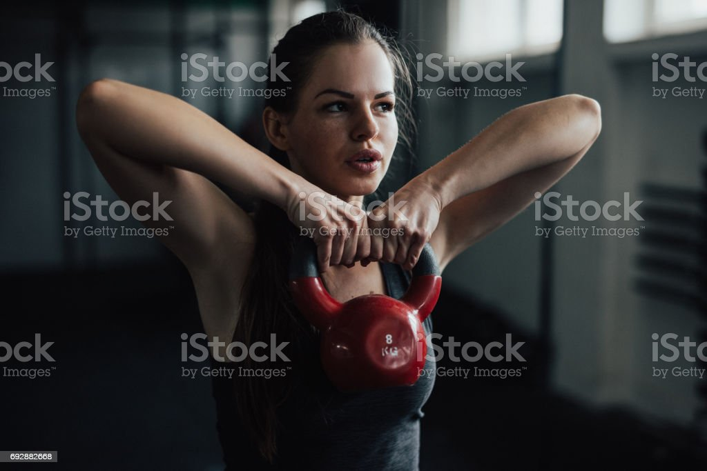 Beautiful girl performing exercise with kettlebell stock photo