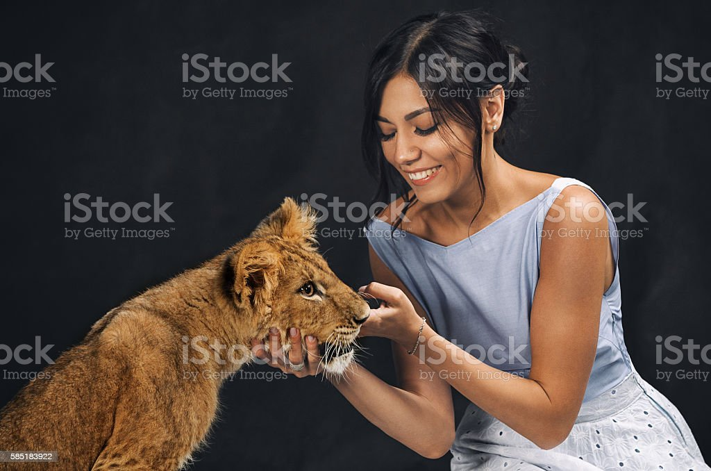 Beautiful girl playing with a lion cub on a black background stock photo