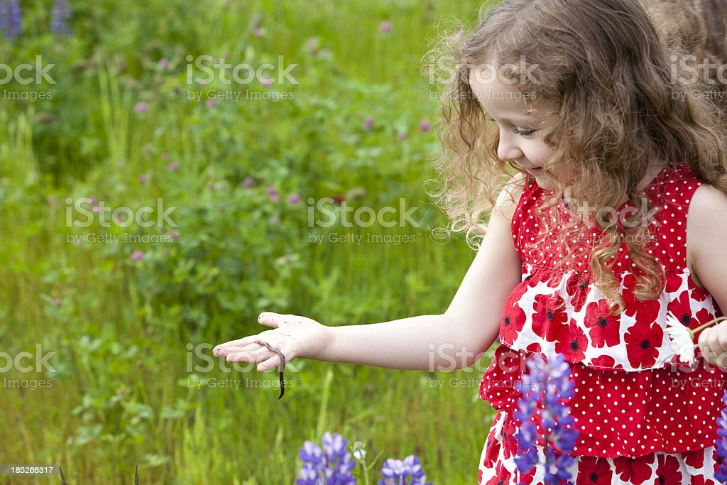 Beautiful girl playing with worm in flower field. stock photo