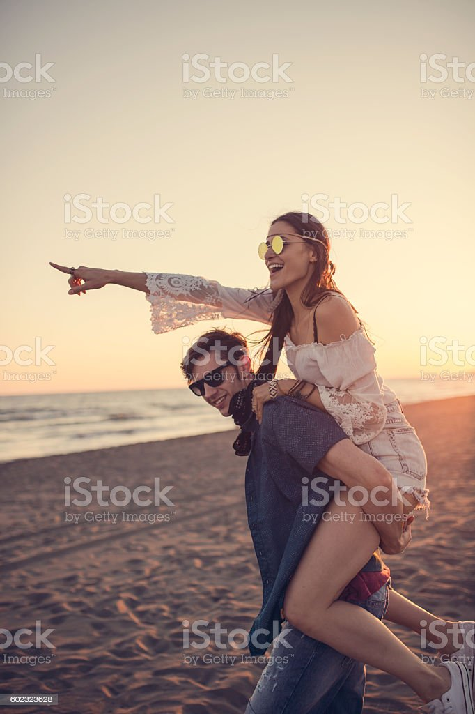 Beautiful girl pointing while riding on her boyfriend back stock photo
