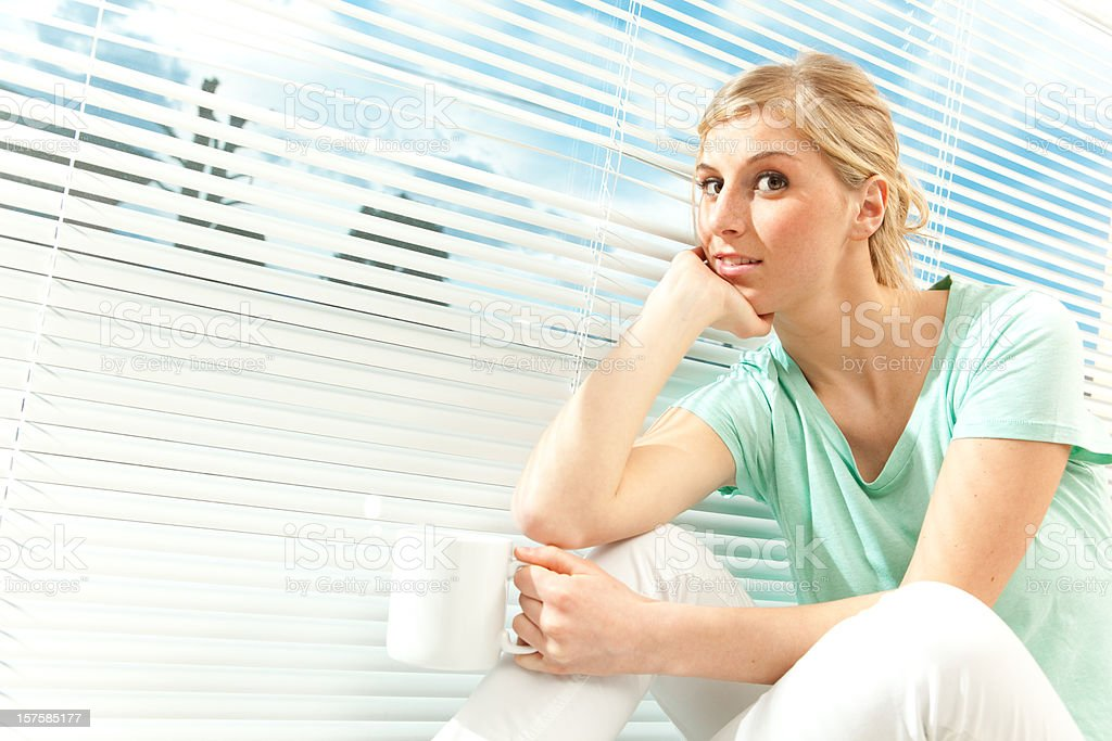 beautiful girl portrait with cup near venetian blind stock photo