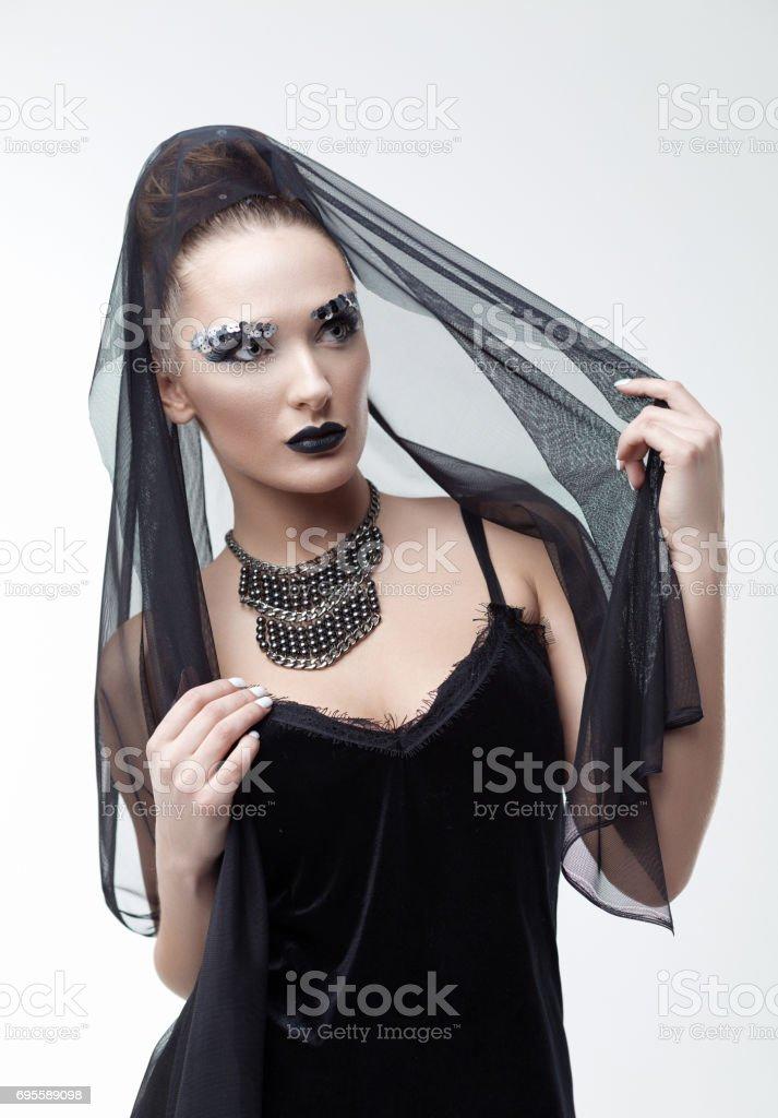 Beautiful girl posing in studio in black veil stock photo