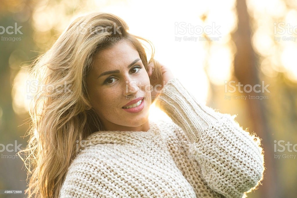 Beautiful girl posing in winter sweater on a sunny day stock photo