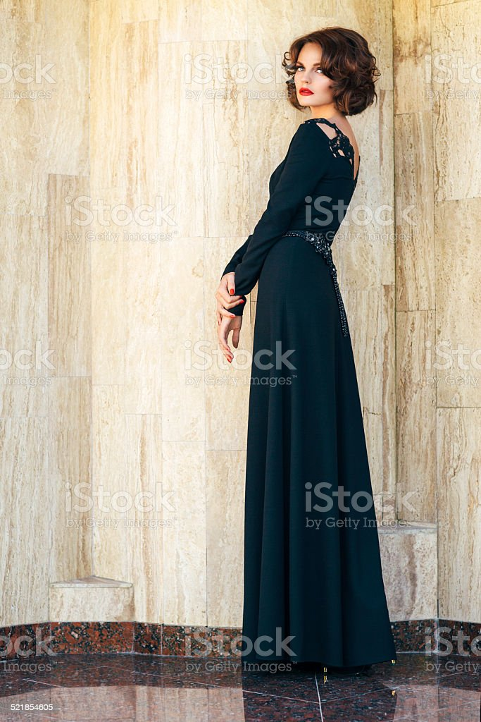 Beautiful girl posing on a background of the marble wall stock photo