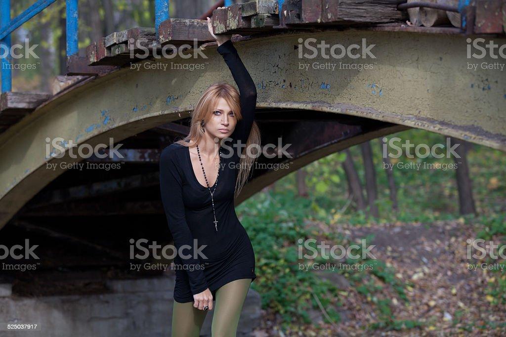 Beautiful girl posing under a pedestrian bridge stock photo