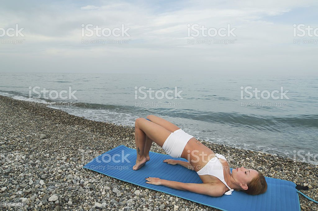 Beautiful girl practicing exercises at the beach stock photo