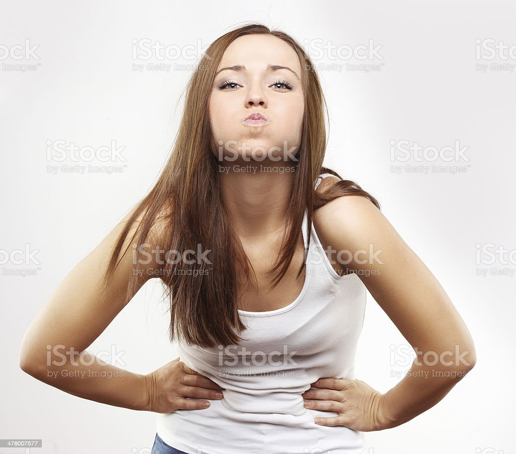Beautiful girl, puffed out his cheeks and blowing royalty-free stock photo