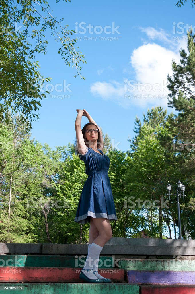 Beautiful girl raised her hands to the sky stock photo