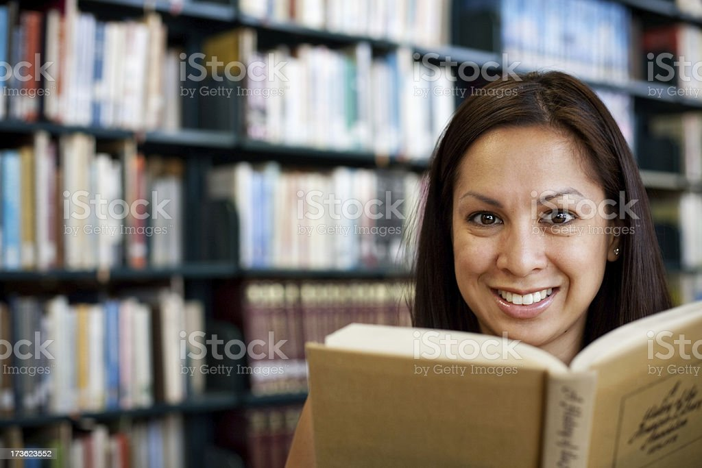 beautiful girl reading a book in the library royalty-free stock photo