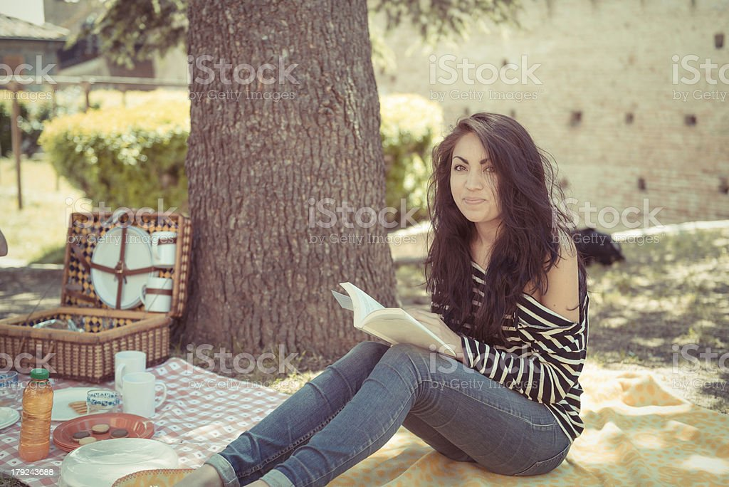 Beautiful girl reading a book in the park stock photo