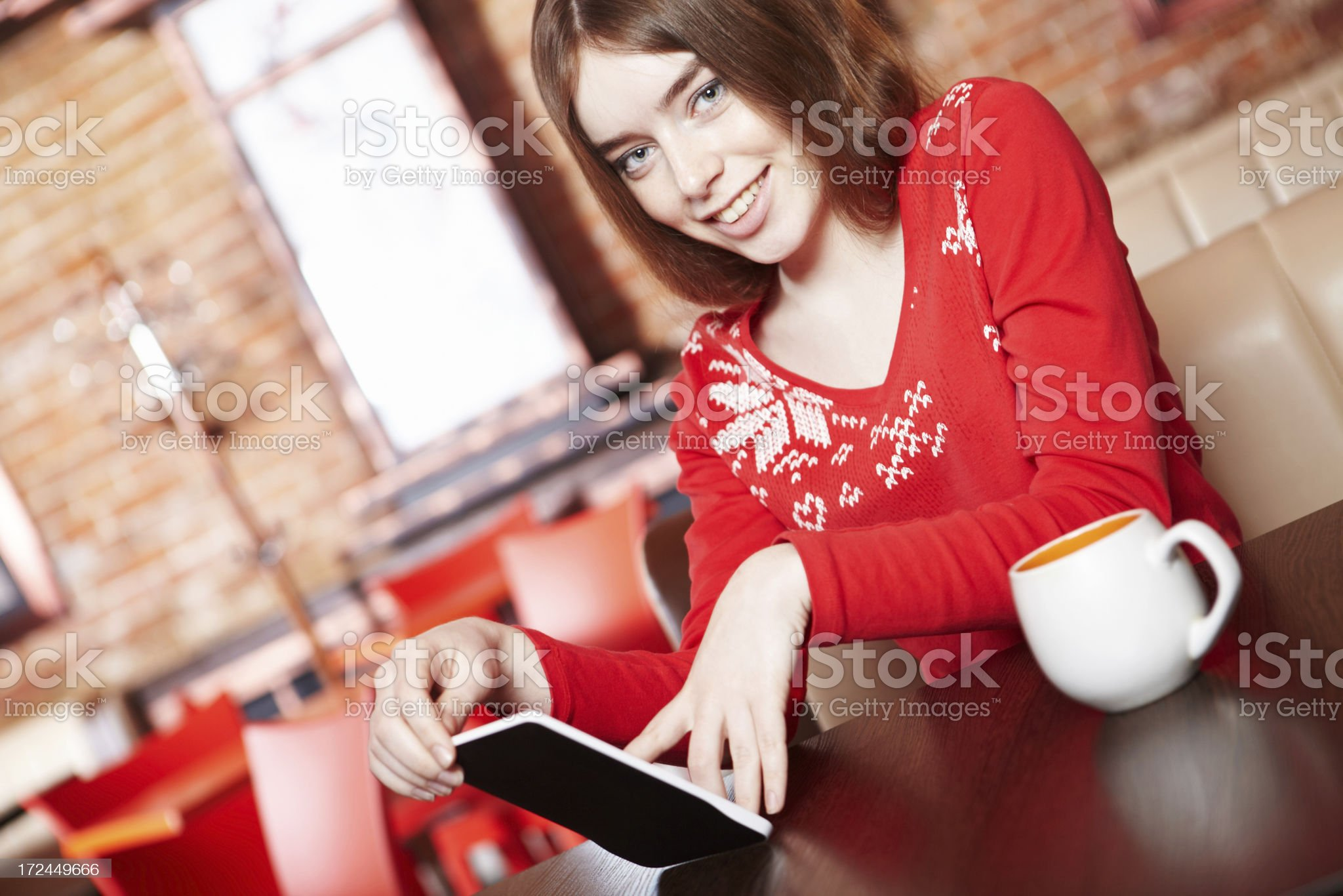 Beautiful girl reading e-book in cafe. royalty-free stock photo