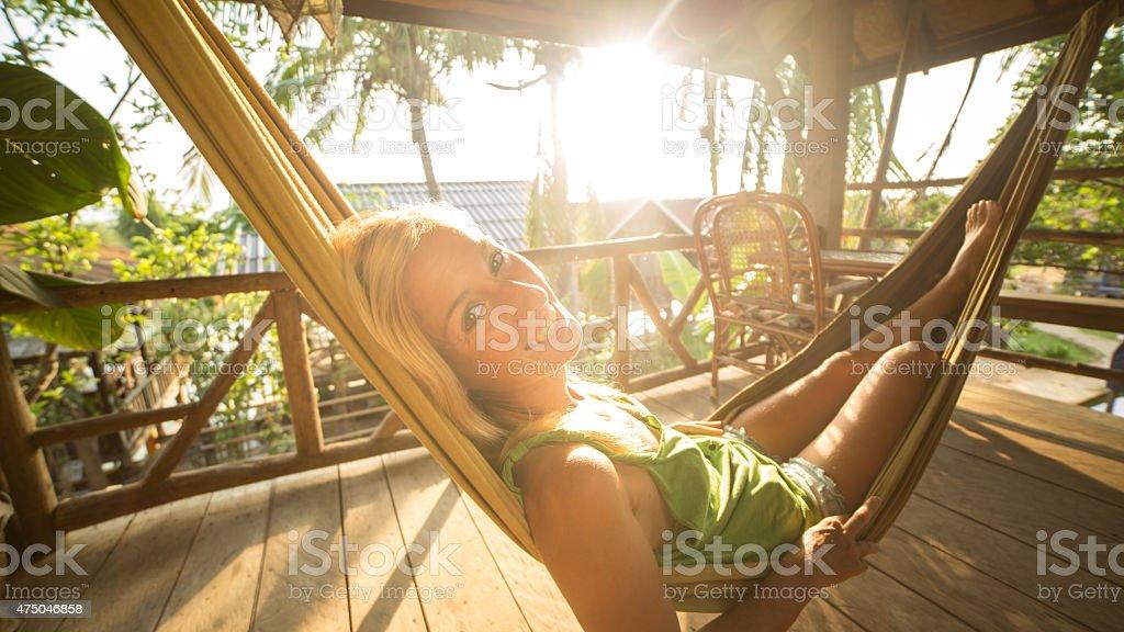 Beautiful girl relaxing on hammock at sunset stock photo