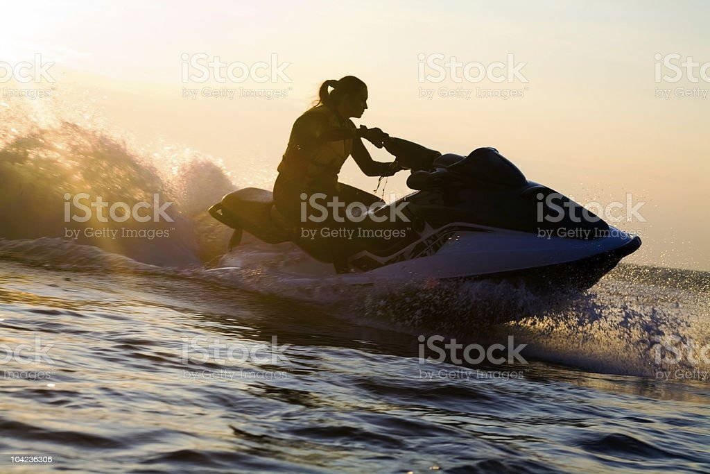 A beautiful girl riding a jet ski during sunset stock photo