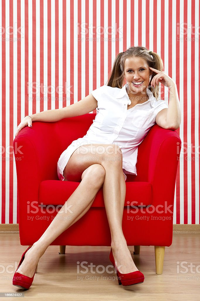 Beautiful girl sat on armchair red portrait royalty-free stock photo