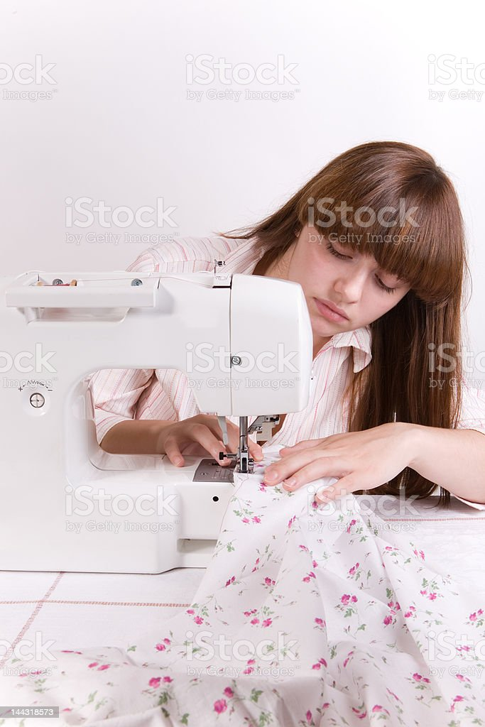 Beautiful girl sewing (vertical) royalty-free stock photo