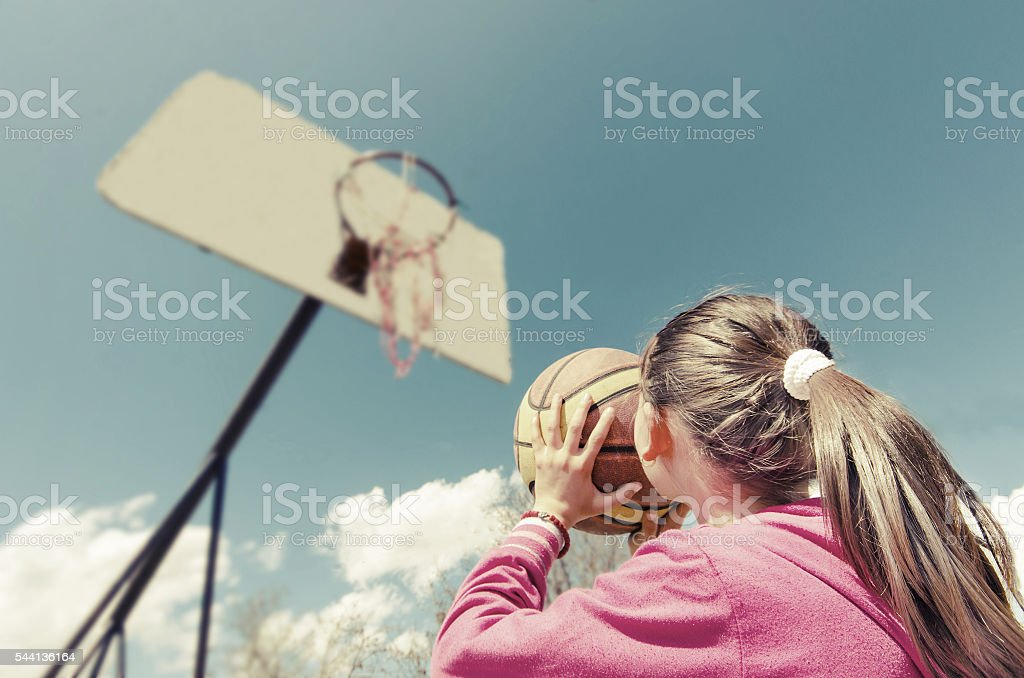 beautiful girl shooting basket and playing basketball stock photo