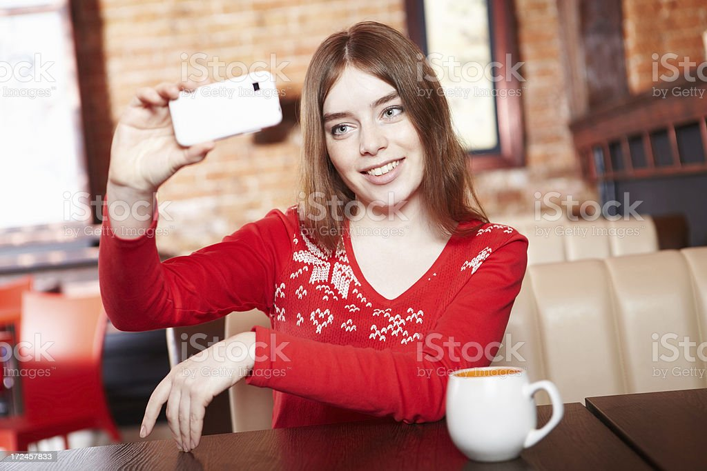 Beautiful girl shooting picture using smartphone in cafe. royalty-free stock photo